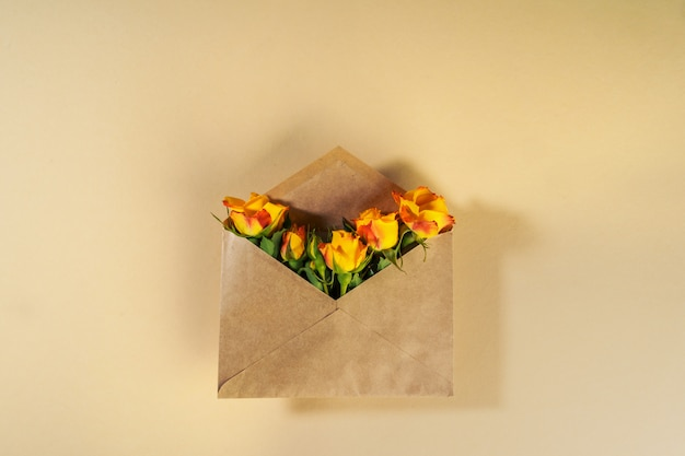 Craft paper envelope with yellow roses on beige surface