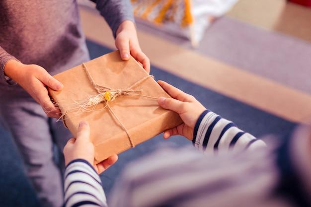 공예 종이. 손을 뻗고 친구로부터 선물 상자를 얻는 십대에 초점을 맞춘 사진