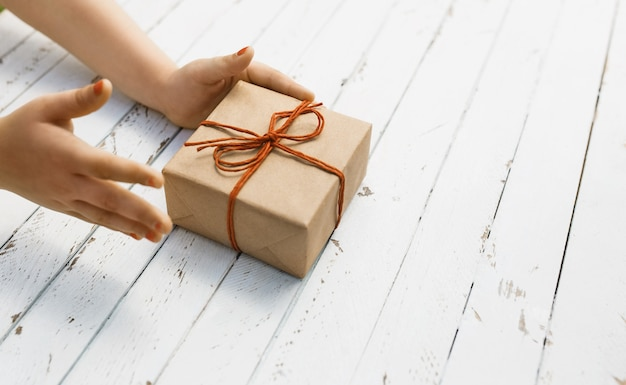 白い木の背景に子供たちの手に赤い弓でクラフト紙ギフトボックス。