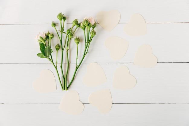 Бумажные сердечки и цветы, белый деревянный фон, плоская планировка