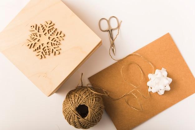 Craft paper near bow, box, scissors, ornament snowflake and twists
