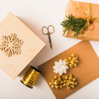 Craft paper near bow, present boxes, scissors, ornament snowflake and ribbon