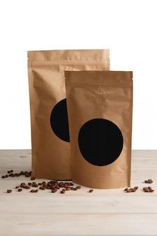 木製のテーブルの上のコーヒーとクラフトペーパーポーチバッグ