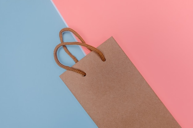 Craft paper shopping bag on paper textured backdrop.