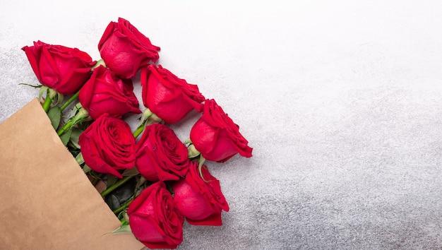 石の背景に花とクラフト紙の買い物袋