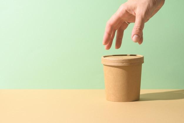 Чашка бумаги ремесла супа и женская рука на коричневой предпосылке. экологическая индивидуальная упаковка. ноль отходов.
