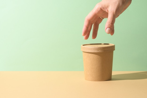 Craft paper soup cup and female hand on brown background. ecological individual package. zero waste.