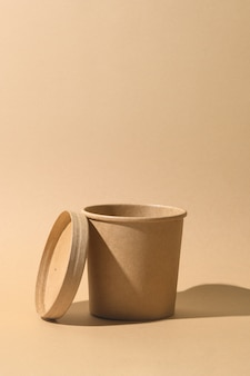 Craft paper soup cup with shadow on brown paper background. empty container. ecological individual package. zero waste.