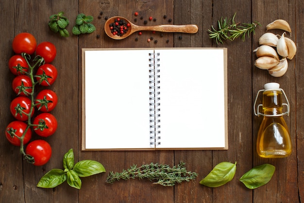 Craft paper with border of vegetables,  herbs and olive oil on a wooden table top view with copy space