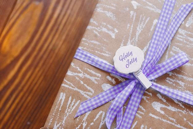 白い抽象的なパターンのクラフト紙。紫の市松模様のリボンで紙に包まれたギフトボックス