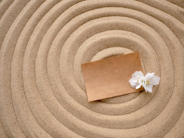 Craft paper with a white flower on the texture of sea sand.