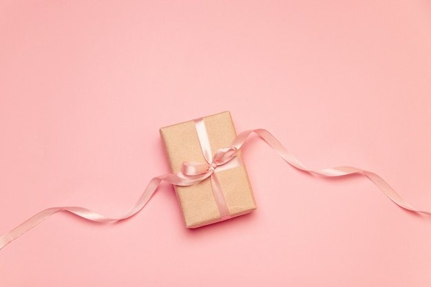 Craft present box with pink pastel bow ribbon on pink canvas