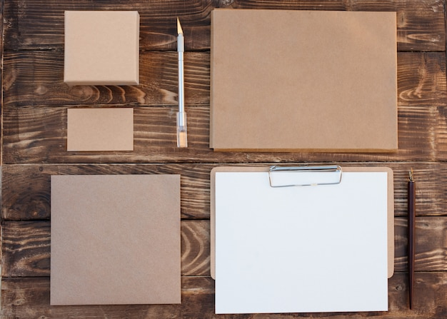 Craft set of empty different items, boxes for gift, envelops, card, sheet, rope on wooden background