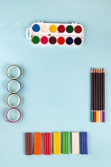 Craft set from multicolored paints, pensils, paper ribbons and plasticine on a pastel blue background. top view