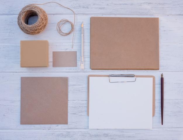 Ремесло набор пустых различных предметов, коробки для подарков, конверты, открытки, лист, веревка на деревянном фоне