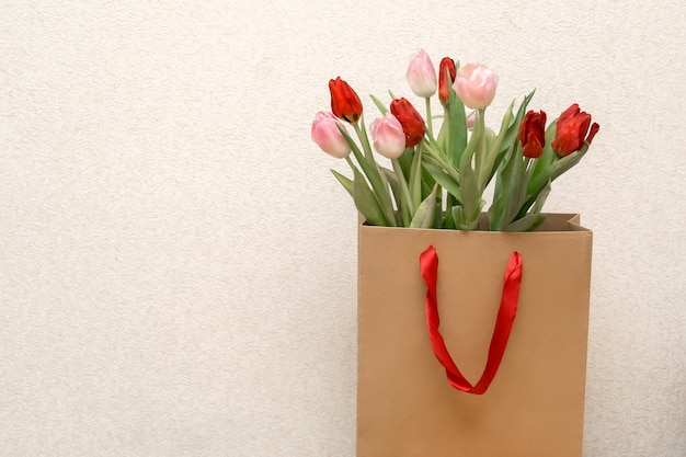 Craft shopping paper bag with flowers close up package with tulips valentines, birthday concept with copy space.