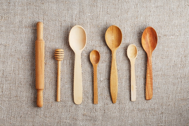 Craft spoons made from different types of wood lie in a row on a hemp burlap fabric