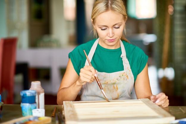 Молодая женщина украшает мебель в craft studio