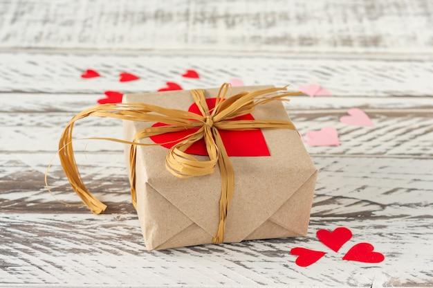 コードの弓と木製の背景に赤いハートのクラフトスタイルの紙のギフトボックス。バレンタインデーと誕生日のお祝いグリーティングカード。