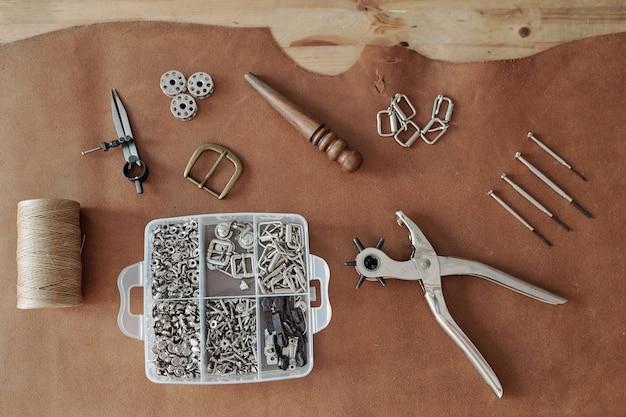 Принадлежности для рукоделия, контейнер с припасами, нитки и другие вещи на куске коричневой замши.