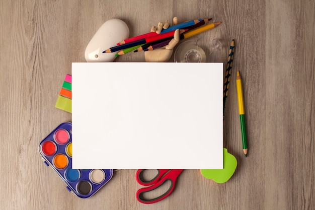 Craft supplies, paints, scissors, computer mouse and blank sheet on wooden table