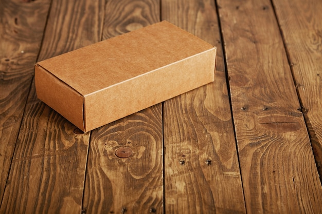 Craft unlabeled cardboard package box presented on stressed brushed wooden table, closeup