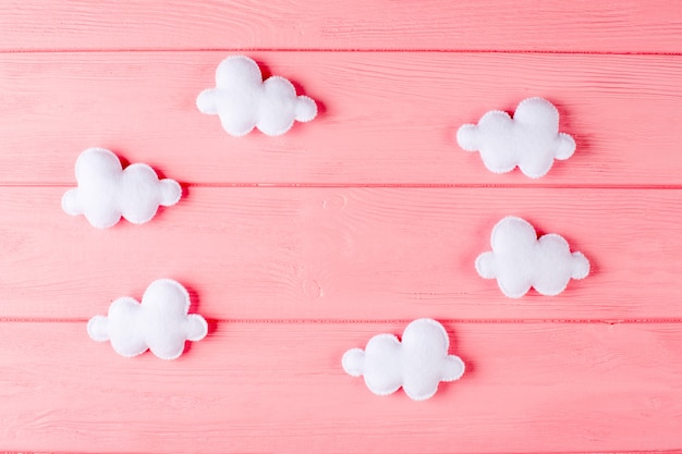 Craft white clouds with frame, copyspace on pink wooden background. hand made felt toys.