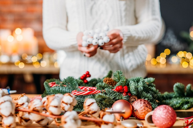 공예 워크샵. 녹색 전나무 나무 나뭇 가지, 목화 식물을 사용하여 크리스마스 인테리어 장식을 만드는 여성 플로리스트.