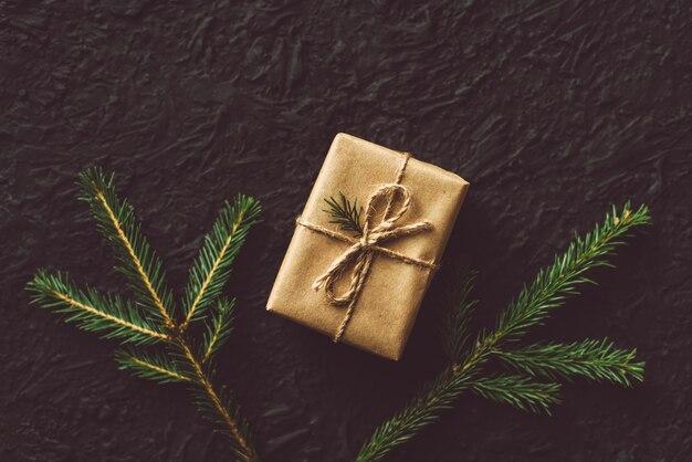 Craft подарочные коробки и еловые ветки на черной стене. вид сверху, плоская планировка, копирование пространства