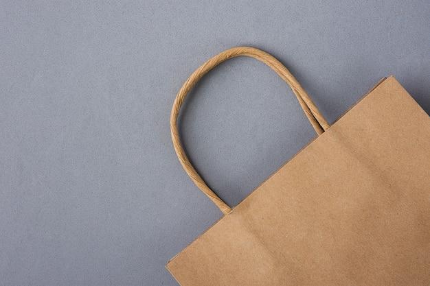 Пустой коричневый craft бумажный мешок на сером фоне. скидки для покупок. черная пятница