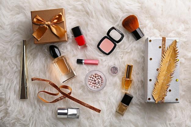 細工されたクリスマスプレゼントと毛皮のような背景に化粧品を作る