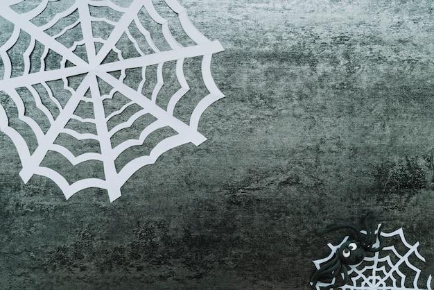 灰色の背景に作られたウェブとおもちゃのクモ