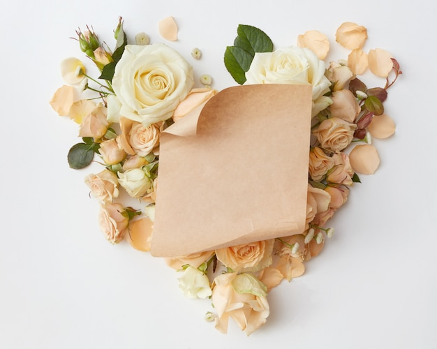 Crafting a piece of paper at the heart of roses isolated, flat lay