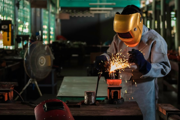 A craftman is welding with workpiece steel.