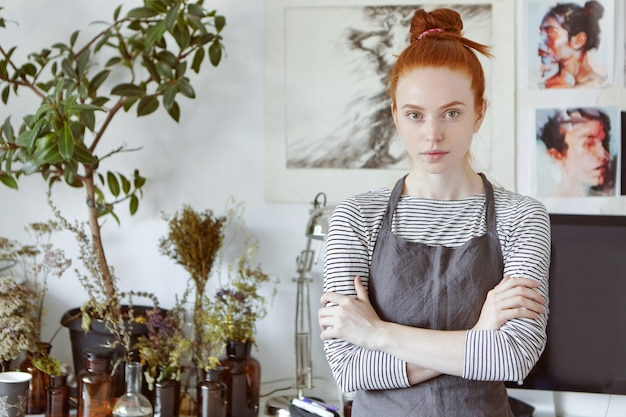 工芸品、芸術、趣味、創造的な職業および職業の概念。ゴージャスな赤い髪のそばかすのある若い女性の職人の屋内ポートレートを上半身で作成し、彼女の創造性を実現する準備ができています