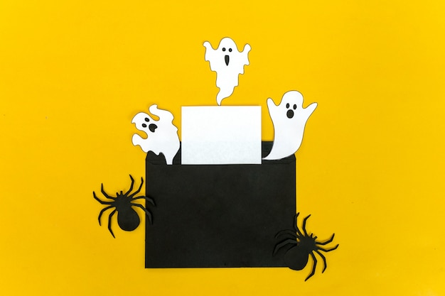 Crafts concept halloween - black bat, cat, ghost from paper on yellow background