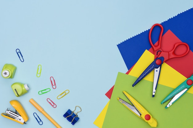 Crafts and scrapbooking preschool education flat lay. tools for creativity with kids at home. colorful scissors with curly blades, paper sheets, punch, pen and mini punch on blue background.