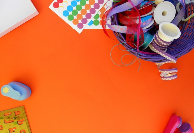 Crafts with colorful ribbons, punches and stickers on an orange background
