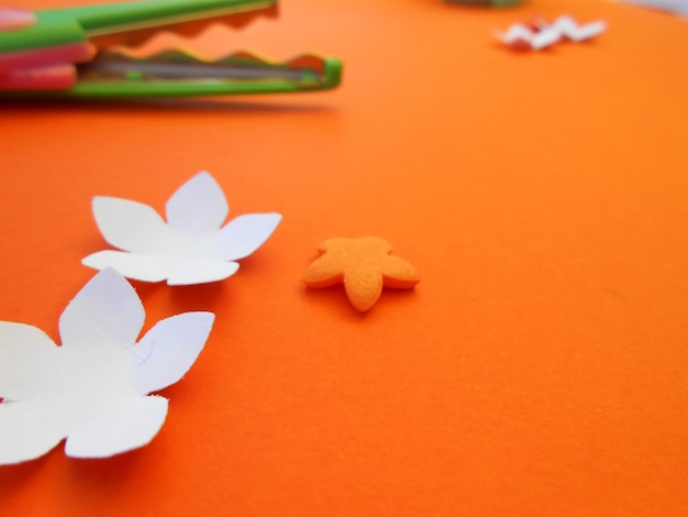 Crafts with paper flowers and scissors on orange background