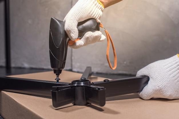 Мастер сборки вращающегося стула с помощью отвертки