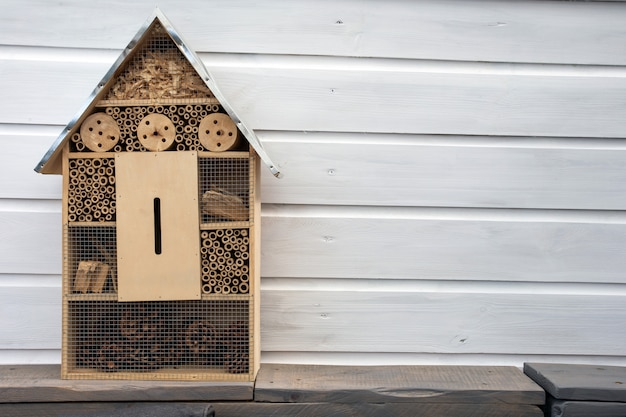 Craftsman built insect hotel decorative wood house with compartments and natural components refuge made to protect and promote ladybugs and butterflies