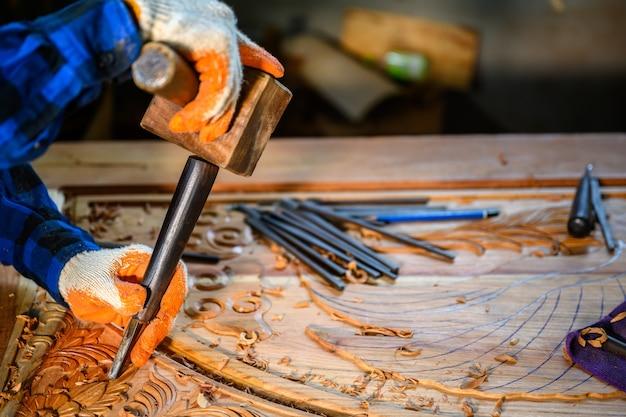 Ремесленник резной по дереву мастера используют деревянные молотки, чтобы лопатой по дереву стамески инструменты столярные работы деревянный фон инженеры создают формы деревьев.