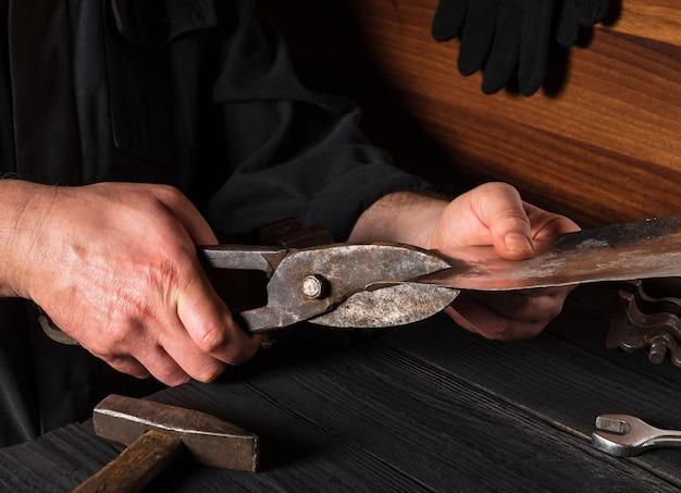 職人が切り鋏で薄いステンレス鋼板をカットします。マスターの手がクローズアップします。ワークショップでの作業環境