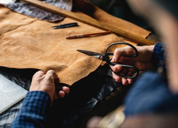 Craftsman cutting into a hide
