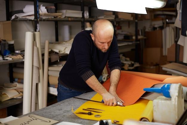 Ремесленник резки кожи с резаком в мастерской