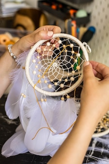 Craftsman female creating ethnic tribal spiritual accessory for protection and luck dreamcatcher