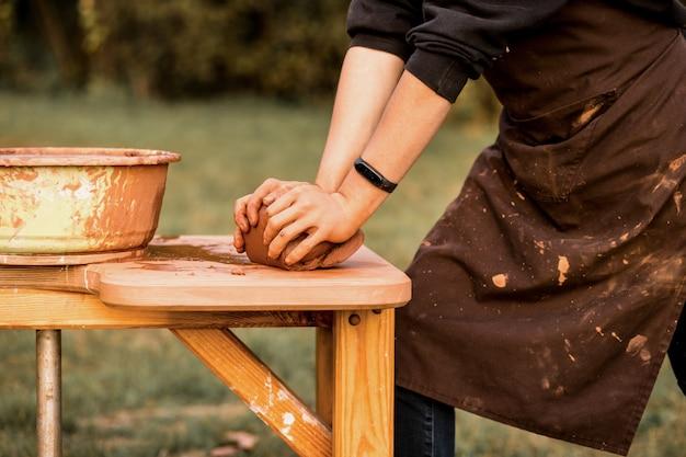 職人の手が陶器のボウルを作るために粘土をこねる屋外でろくろに取り組んでいる男