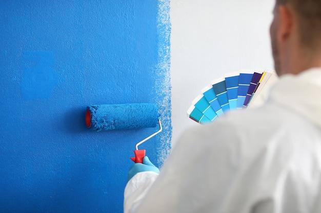 職人はローラーとカラーパレットを持ち、白い壁を青く塗っています。壁の塗装サービスと塗装コンセプト