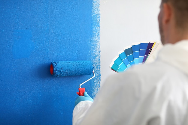 Мастер держит валик и цветовую палитру и красит белую стену в синий цвет. услуги по покраске стен и концепция покраски