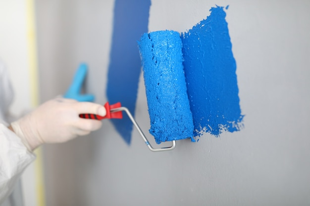 Craftsman holds roller and paints white wall blue. painter services concept